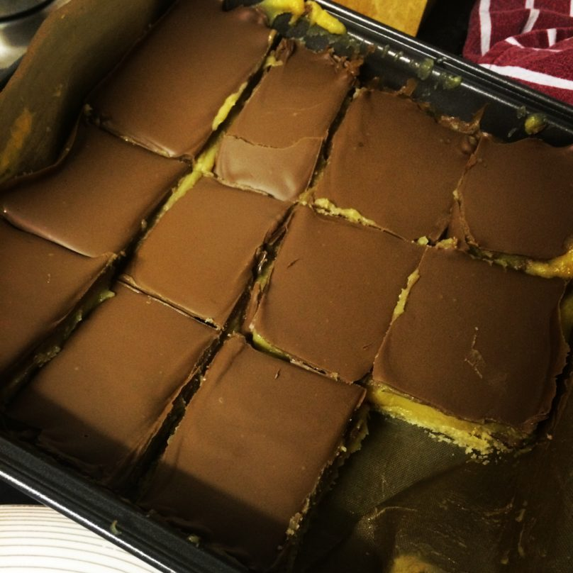 The finished millionaires shortbread in a black baking tray with one piece missing