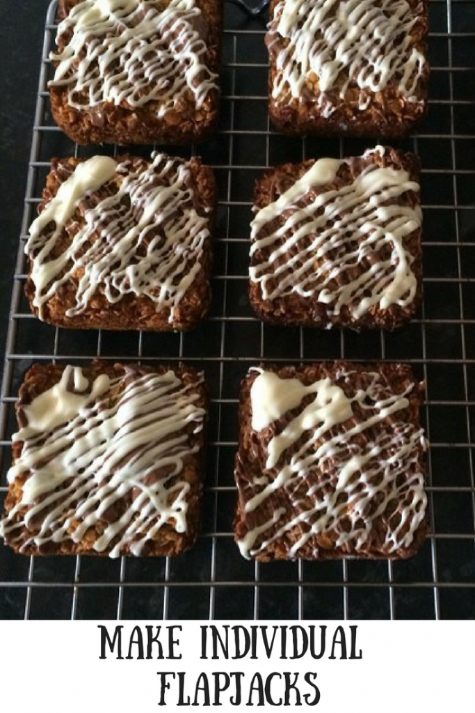 Individual flapjacks on a cooling rack with white icing decoration and text overlay that says make individual flapjacks