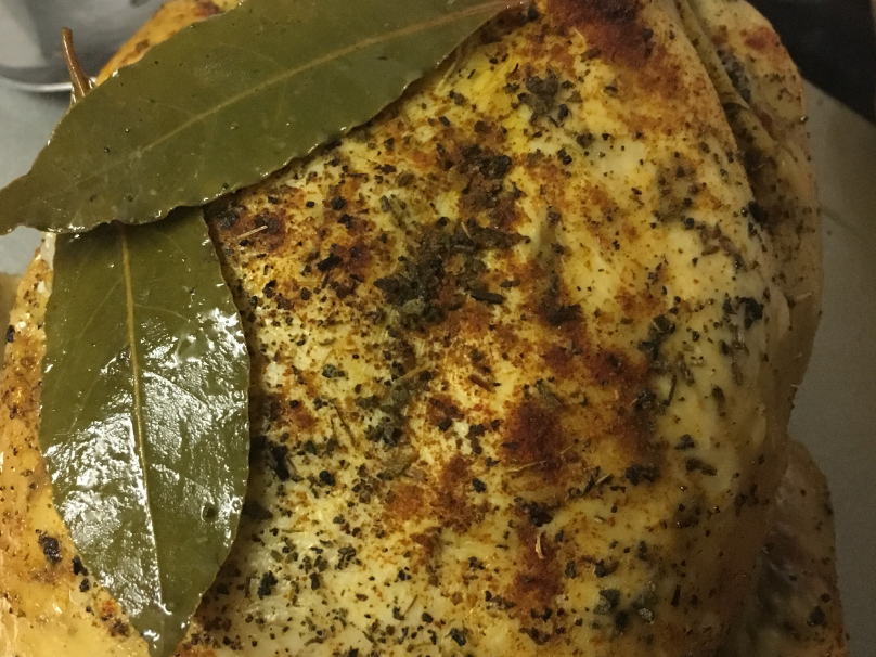A cooked slow cooker whole chicken with bay leaves on it and seasoning
