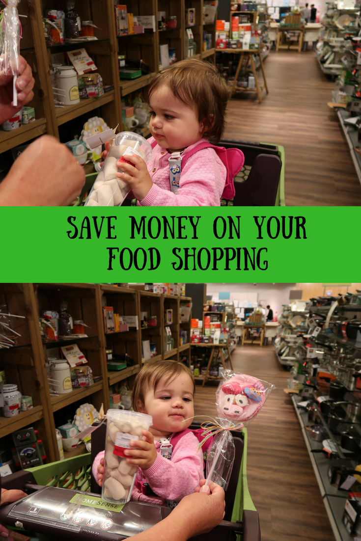 Daisy sitting in a trolley in a Homesense store holding a lolly and a tub of marshmallows with text overlay that says save money on your food shopping.