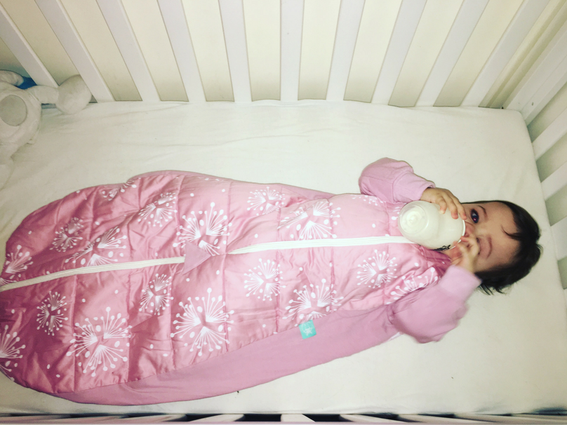 Daisy in her cot in a sleeping bag drinking from a bottle while half asleep