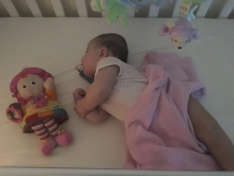 Daisy sleeping in her cot with a Lamaze toy