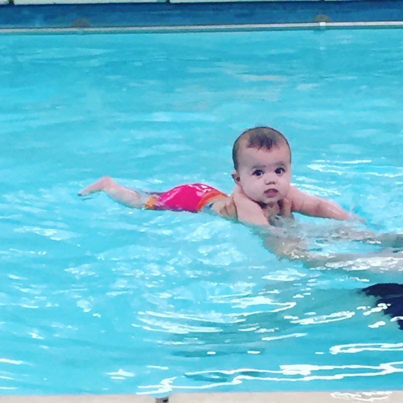 A baby swimming in a swimming pool during Water Babies lessons