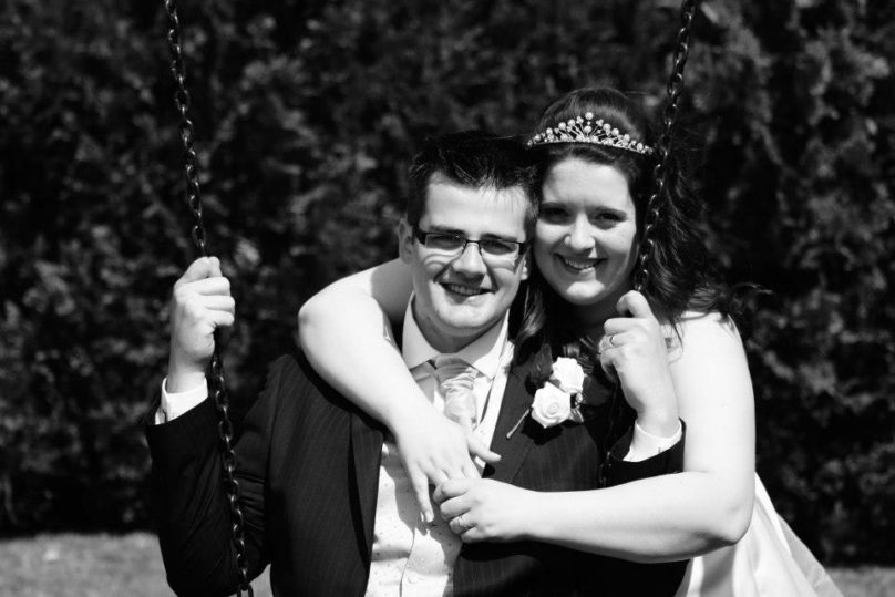 Katy and Tom on their wedding day on a swing