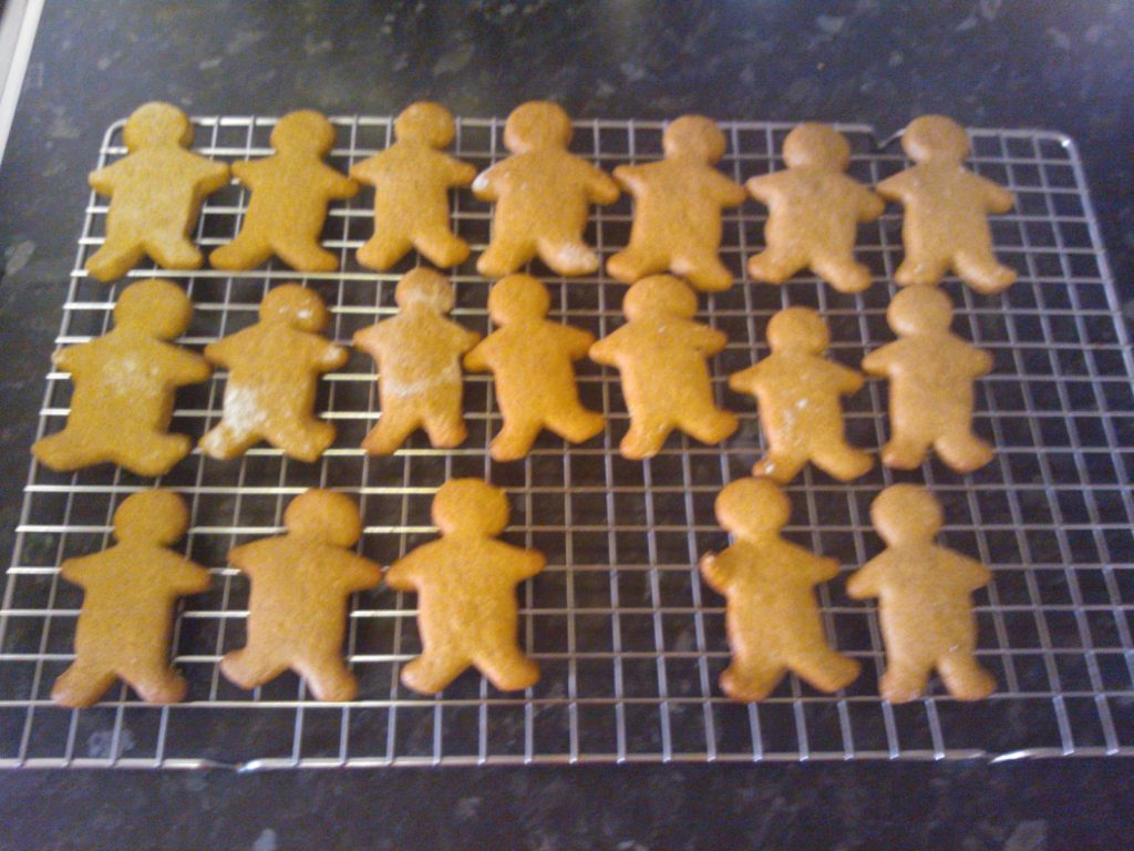 A tray of baked gingerbread men on a cooling rack