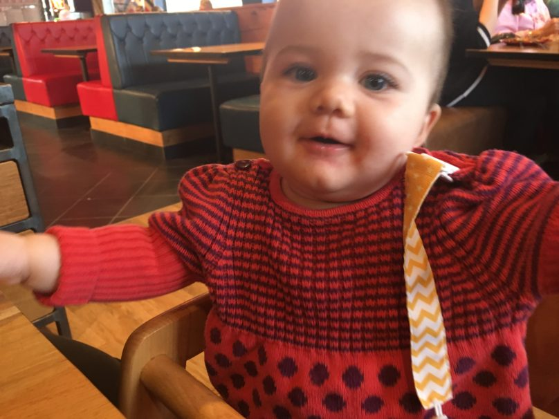 Daisy at eight months old sitting in a high chair wearing a red jumper