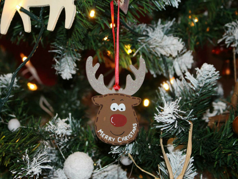 A reindeer Christmas tree ornament that says Merry Christmas