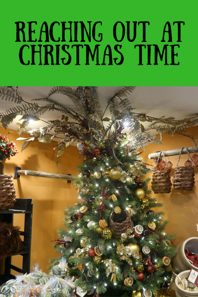 A festive Christmas tree with a lemon bauble theme and text overlay that says reaching out at Christmas time