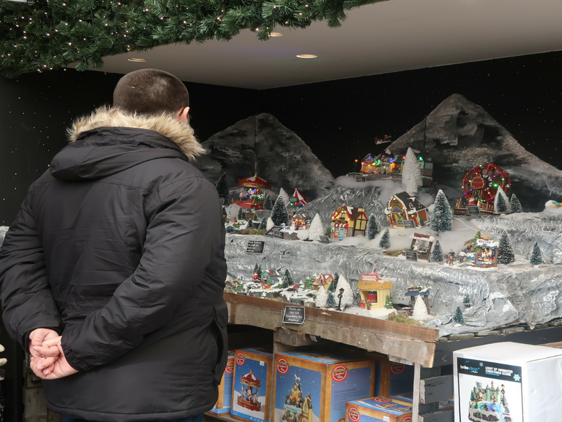 Thomas standing by a Christmas light up scene in a garden centre