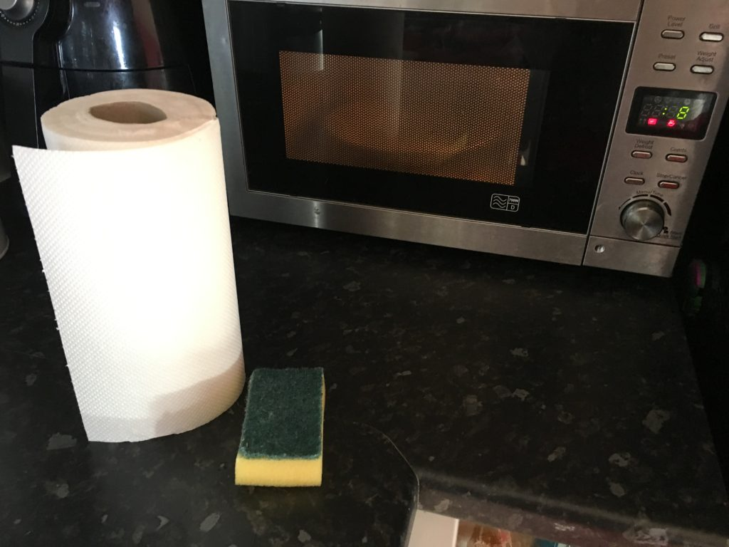 Kitchen towel and a sponge ready to clean in the microwave