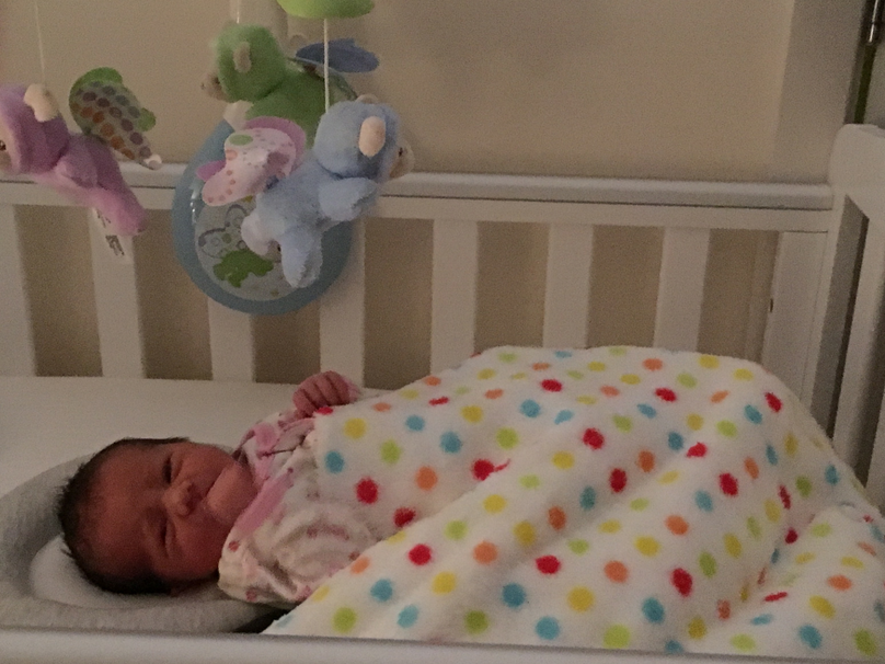My small baby sleeping in her cot with a mobile overhead and a blue, green, orange, yellow and red spotty white blanket.