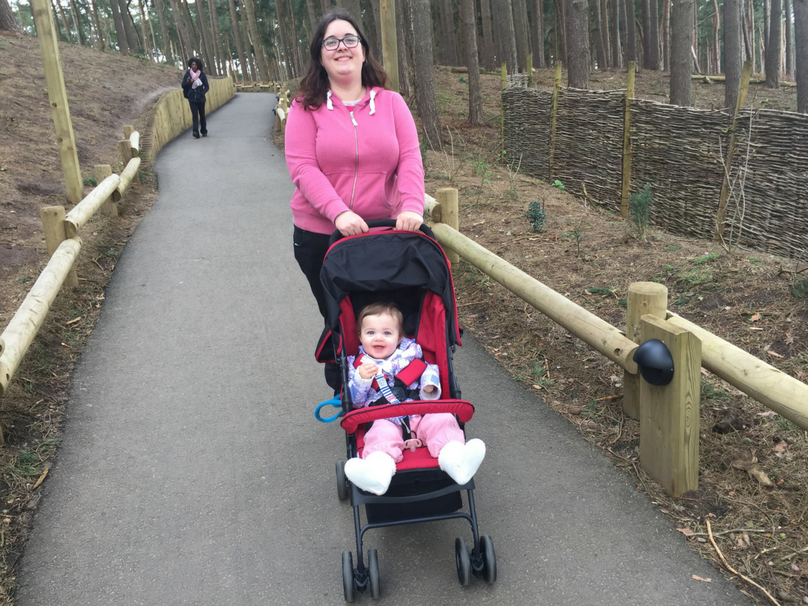 Katy pushing Daisy in a pram on holiday in Centerparcs Woburn Forest.