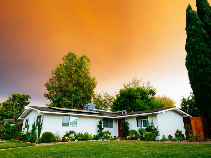 A single storey home surrounded by trees with an orange sunset sky.