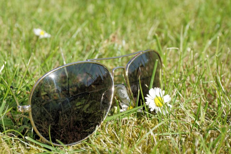 A pair of sunglasses on a patch of grass with a daisy