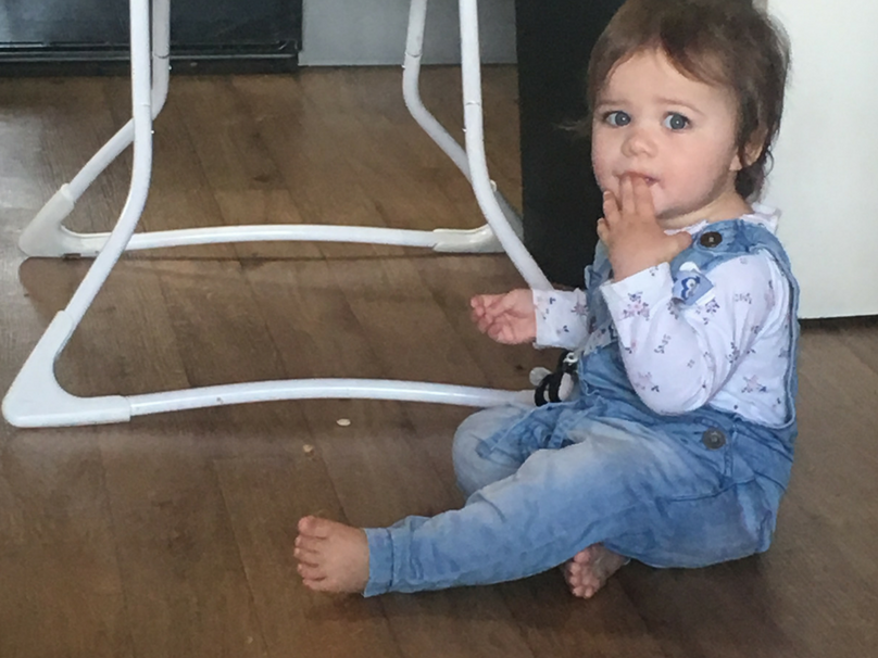 Daisy eating a bit of floor candy at 15 months old
