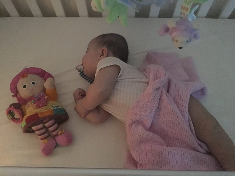 Daisy sleeping in her cot with a Lamaze doll