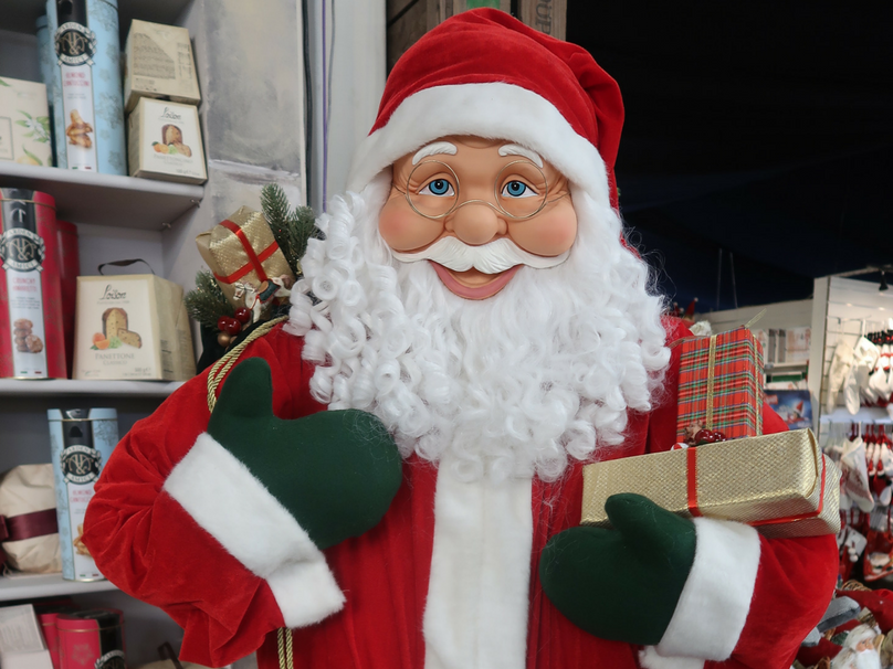 A Santa ornament holding presents in a garden centre