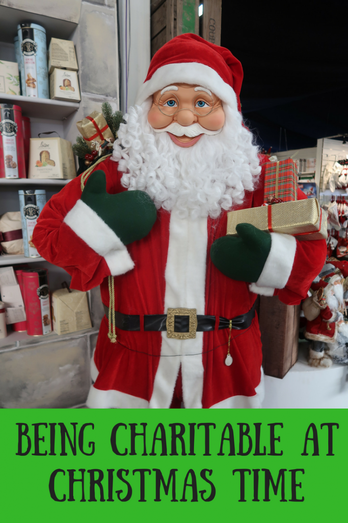 A Santa ornament in a garden centre with text overlay that says being charitable at Christmas time