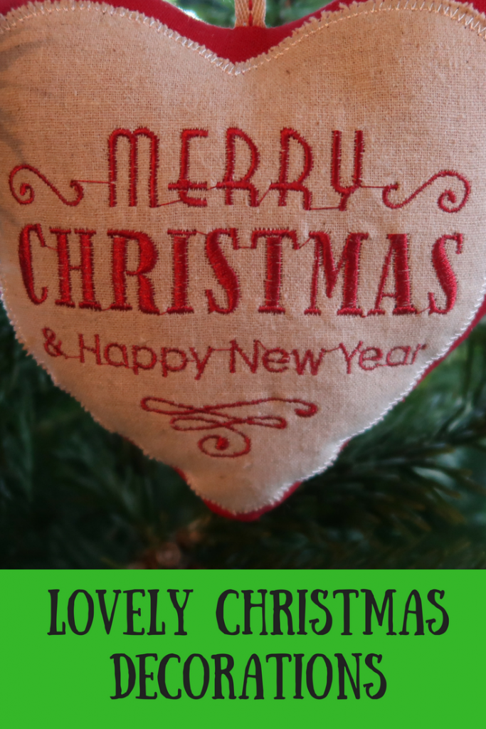 A fabric heart Merry Christmas ornament in a fir tree with text overlay that says lovely Christmas decorations