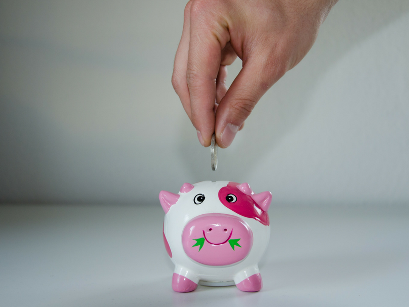 A pink piggy bank with a hand putting a silver coin into it