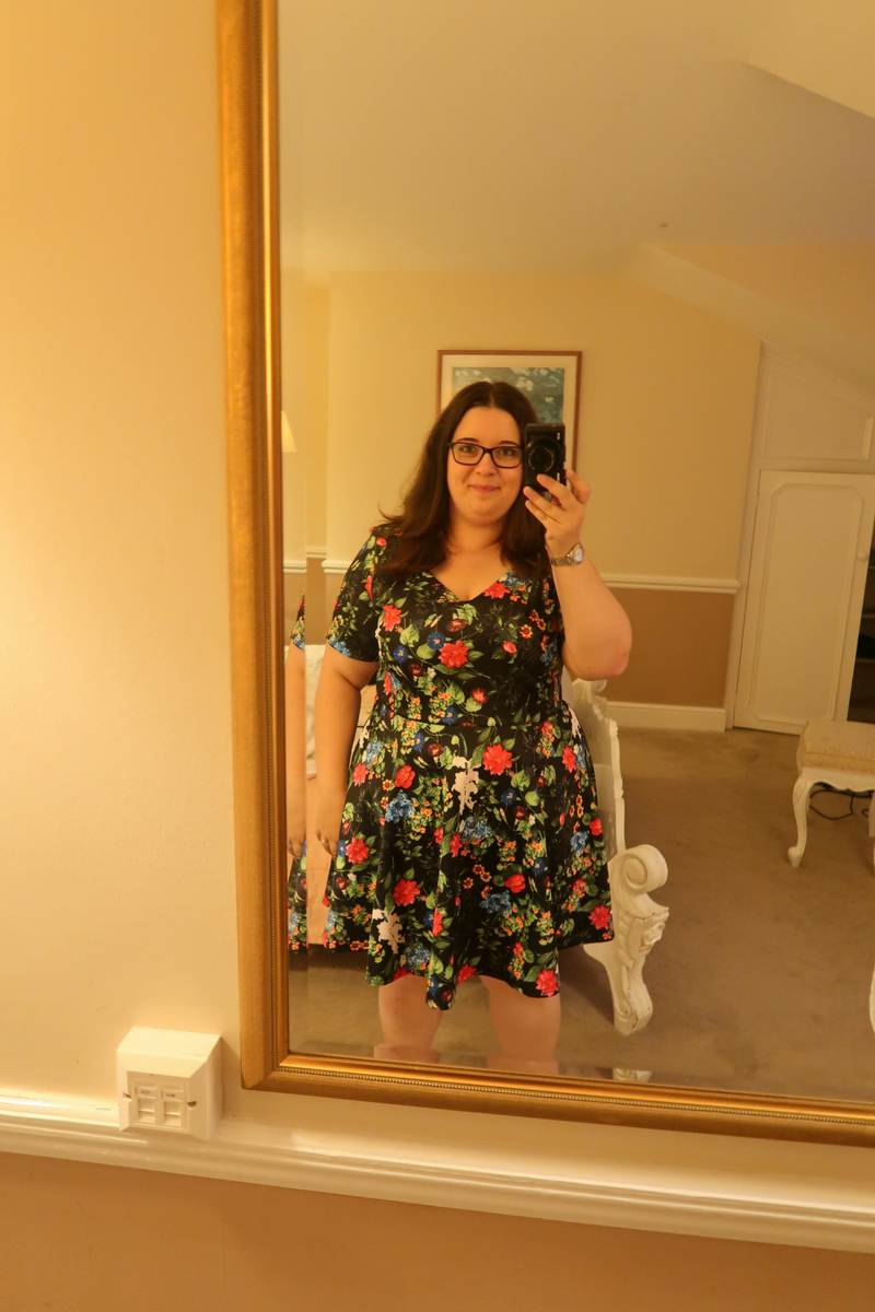 Katy taking a photo in a full length mirror while wearing a floral dress with the Canon G7X Mark II