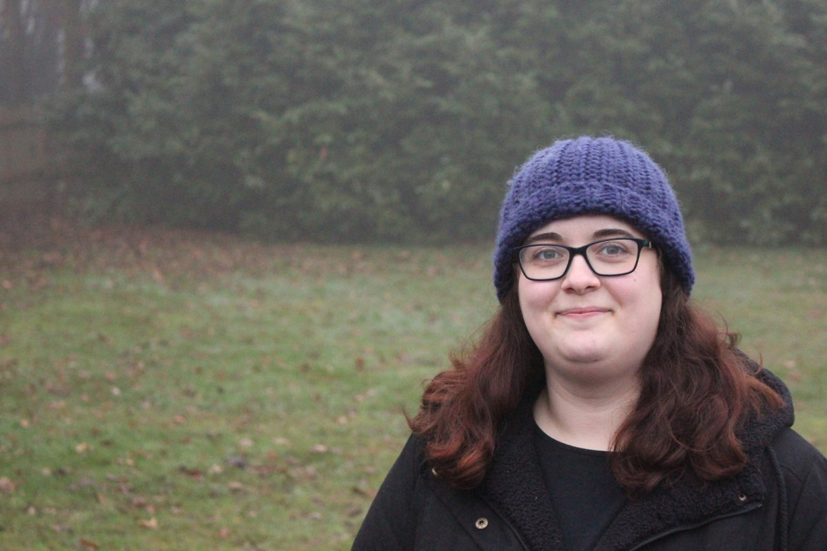 A photo of Katy Stevens, from Katykicker, wearing a black coat, black top and blue hat in a foggy field. Katy wears glasses and smiles into the camera.