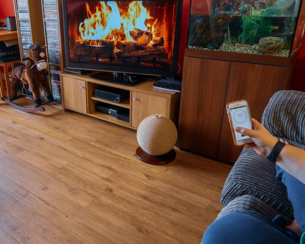 Katy sitting on the sofa, in front of a fire on the TV, using an energy app on her mobile phone