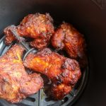 Four cooked air fryer chicken wings in the air fryer basket