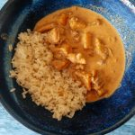 Slow cooker tikka masala with white rice, dusted with coriander, in a blue ramen bowl