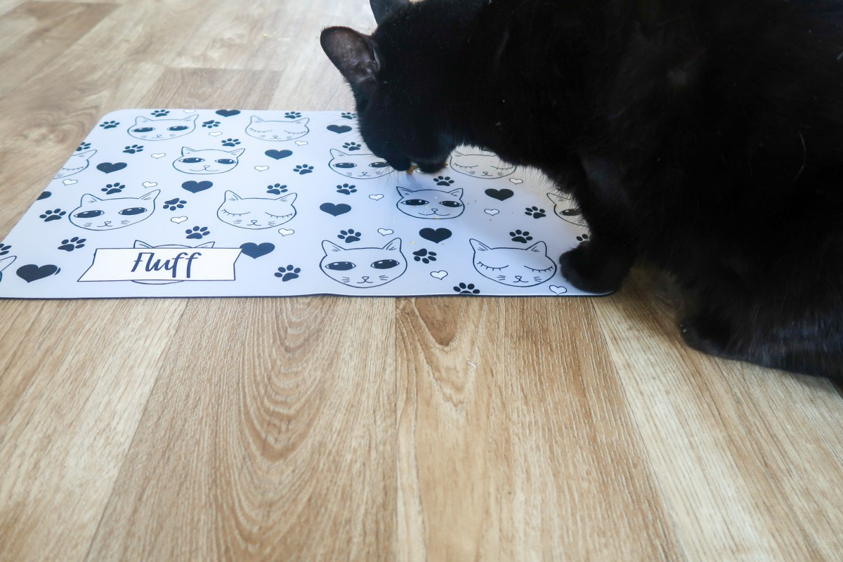 A black cat eating cat treats from a grey and black cat mat that displays the word Fluff