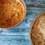 A cooker slow cooker chicken tikka masala, with rice and coriander on a blue backdrop