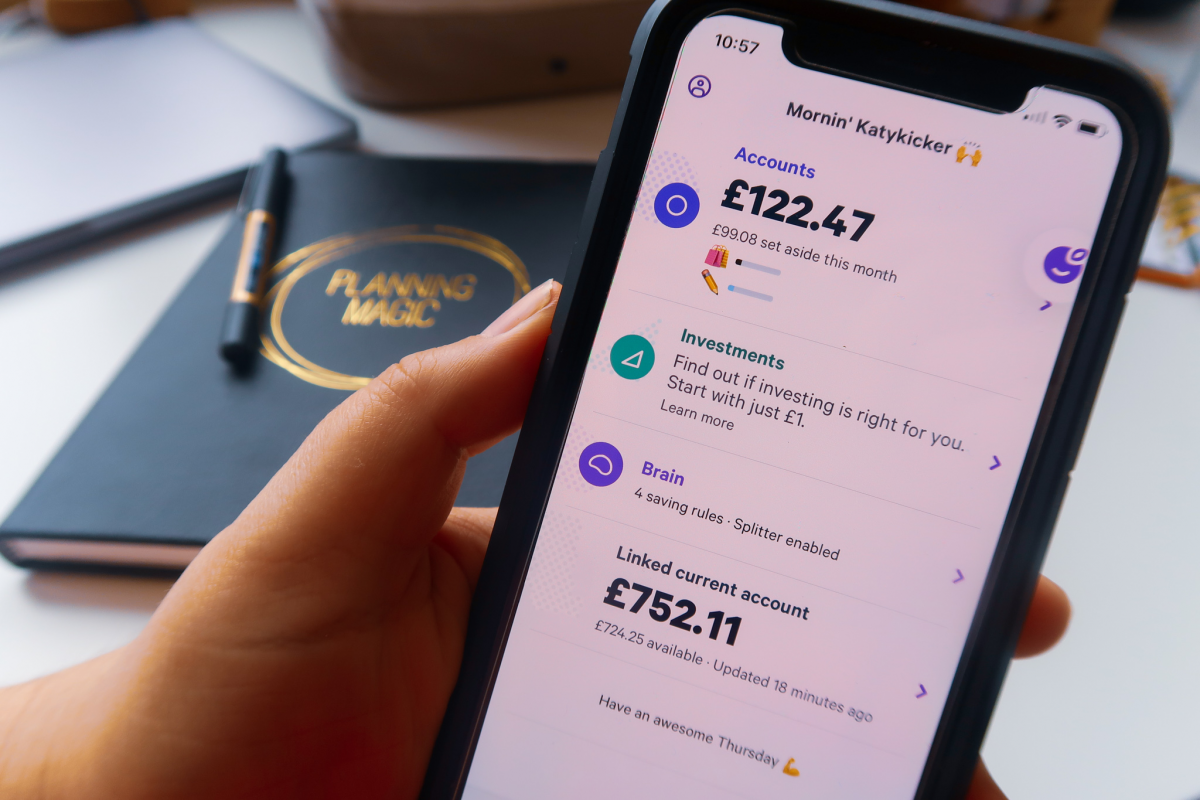 A hand holding an iPhone with the Plum finance app displaying accounts £122.47, linked current account £752.11 with £724.25 available.