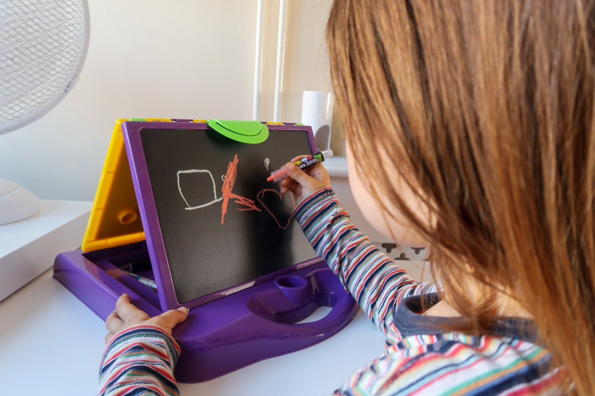 Daisy using the chalkboard on the Little Brian Mini Art Station