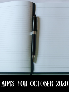 A notebook and pen with text overlay that says aims for October 2020