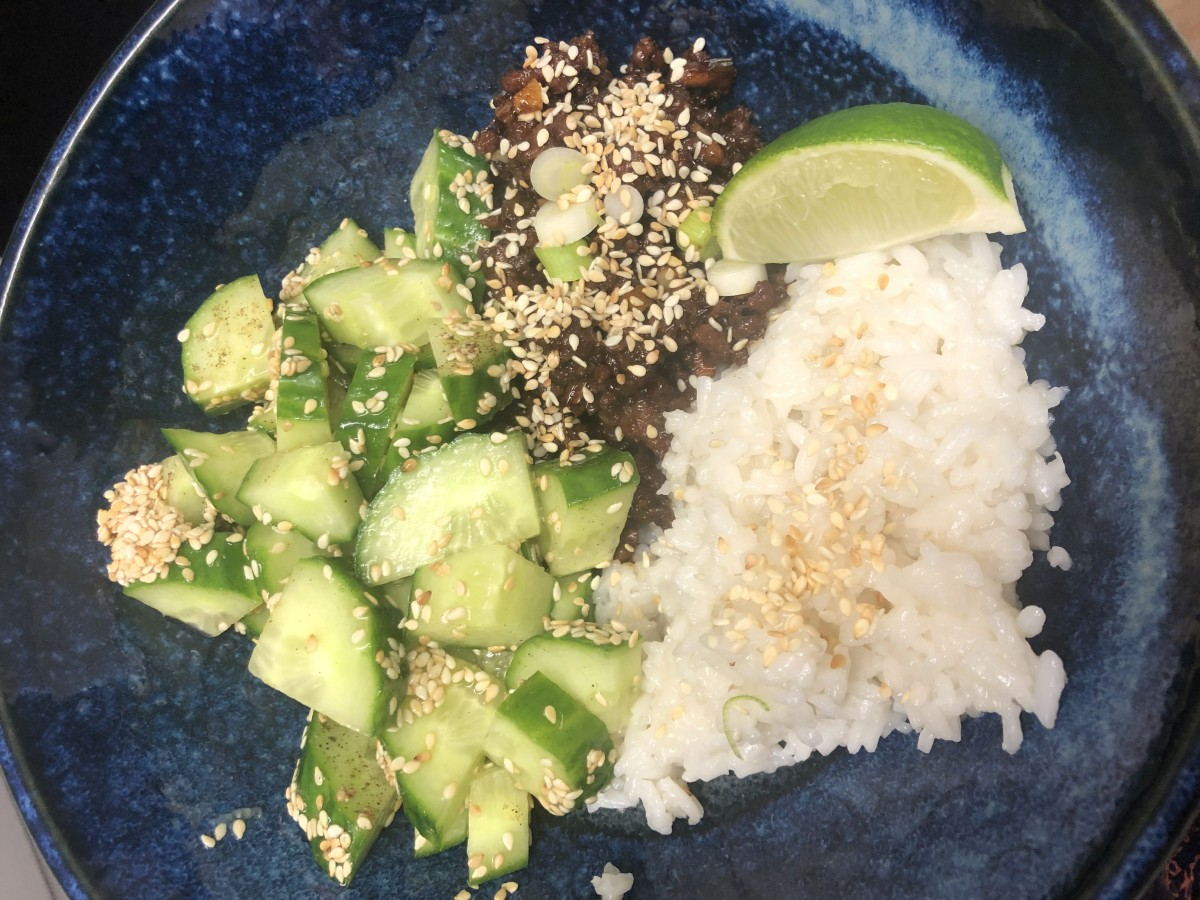 Hello Fresh dinner with cucumber, rice and minced pork with lime wedges and sesame seeds