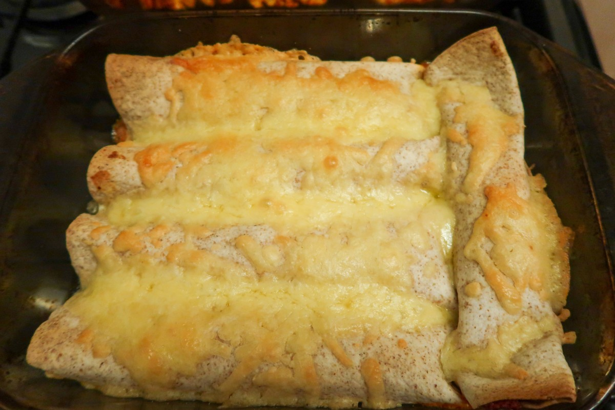Cooked slow cooker beef enchiladas in an oven dish