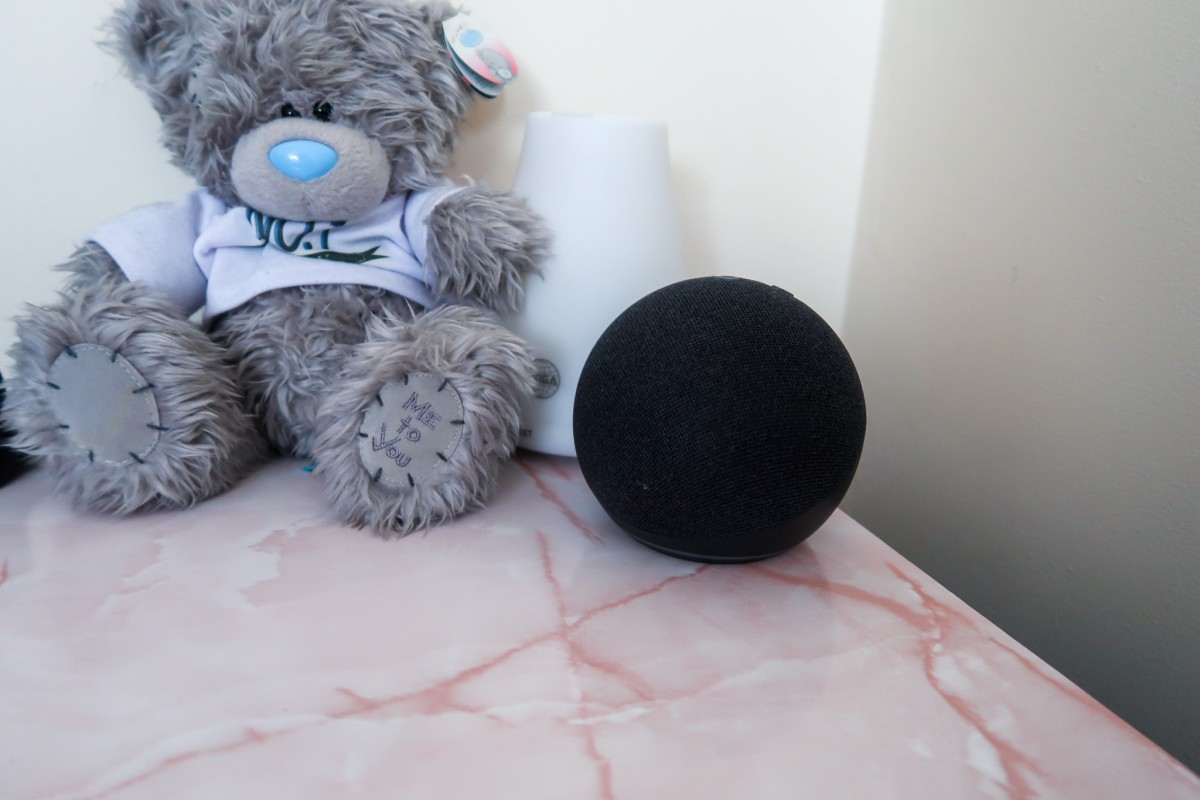 A bedside tablet with pink marble effect top, a me to you teddy that says 'no 1 father' and an Amazon Echo dot 4th generation device