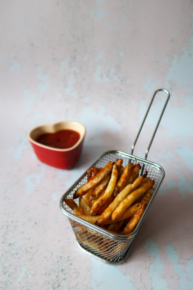 Air fryer fries in a basket with ketchup