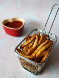 Healthy Airfryer chips in a fries basket with a heart shaped ramekin of tomato ketchup