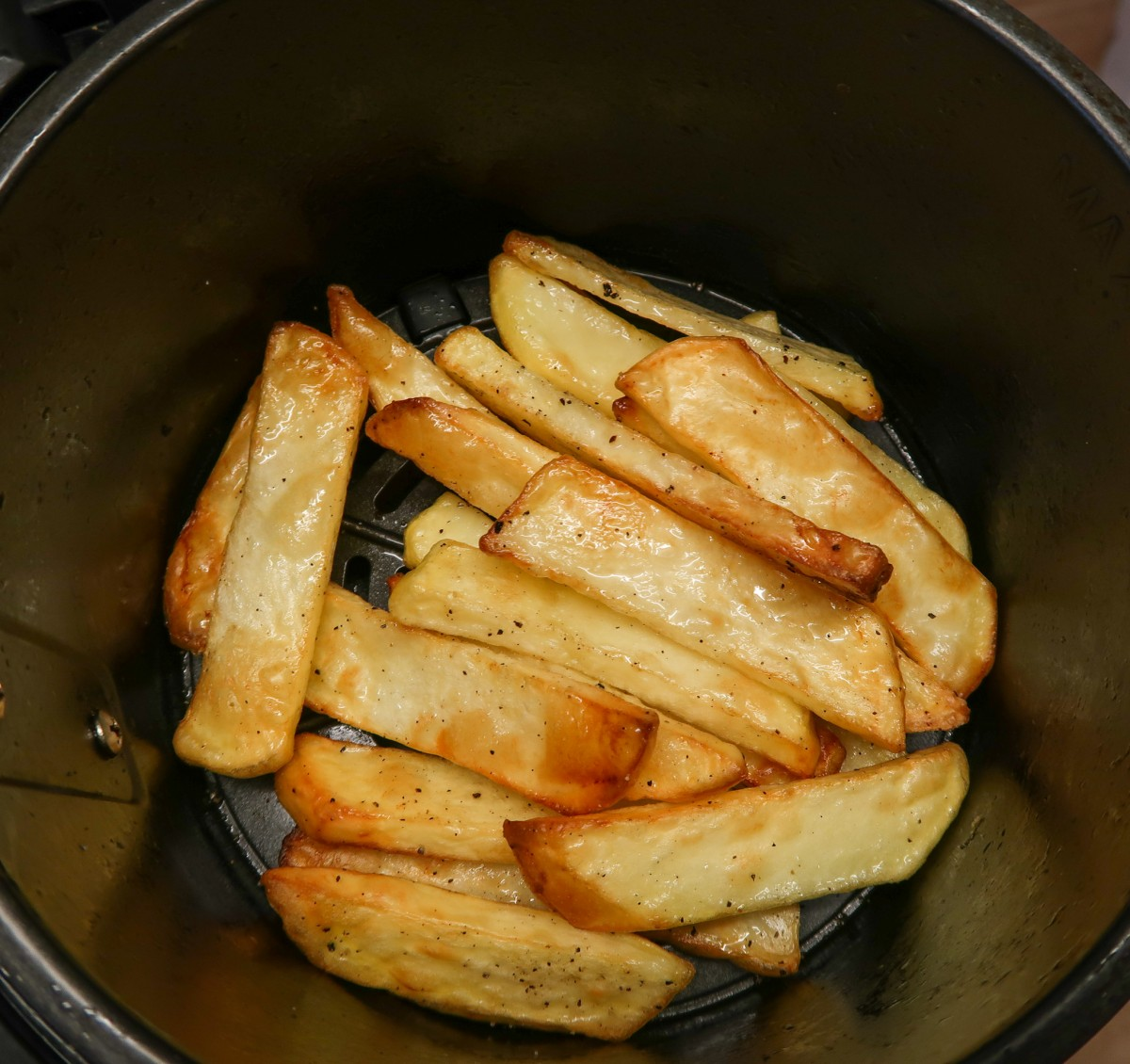 Chunky chips in the air fryer with salt and pepper after cooking