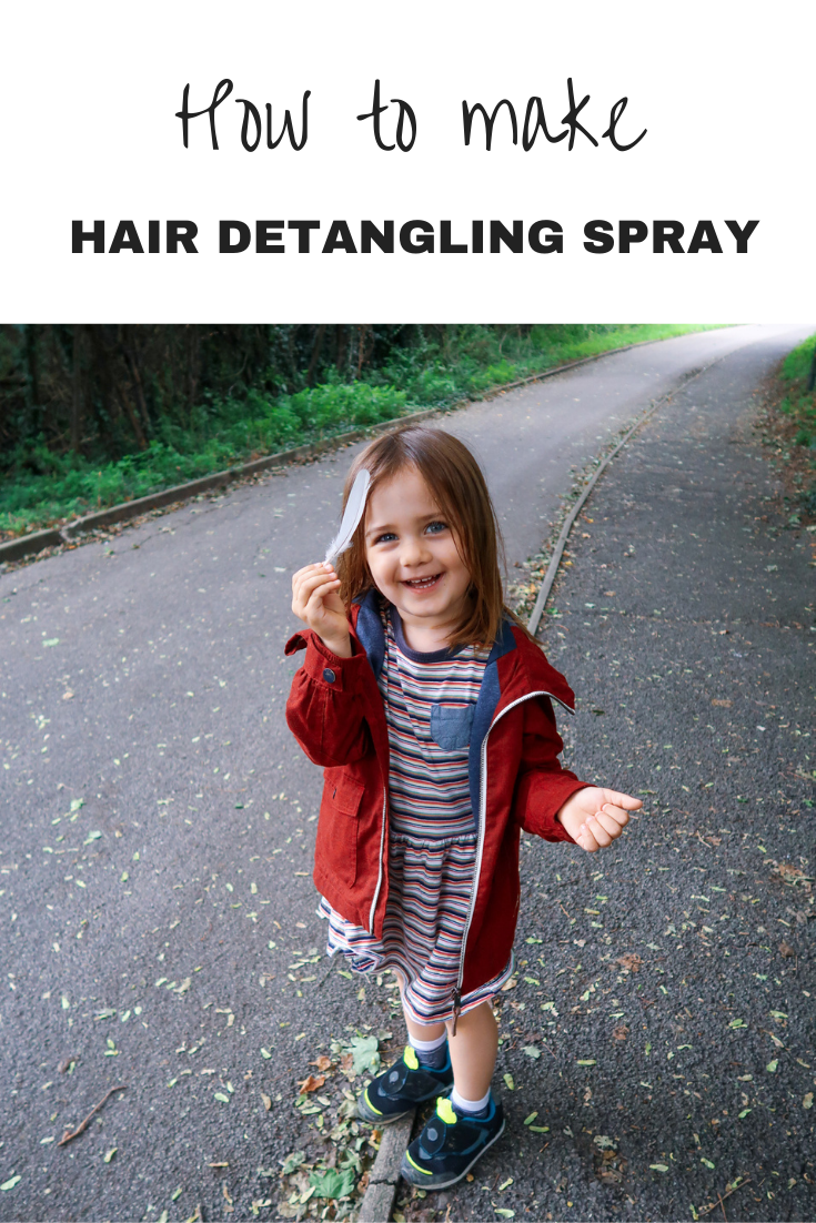 Daisy in a stripy dress, red jacket and black trainers holding a bird feather on a footpath with text overlay that says how to make hair detangling spray
