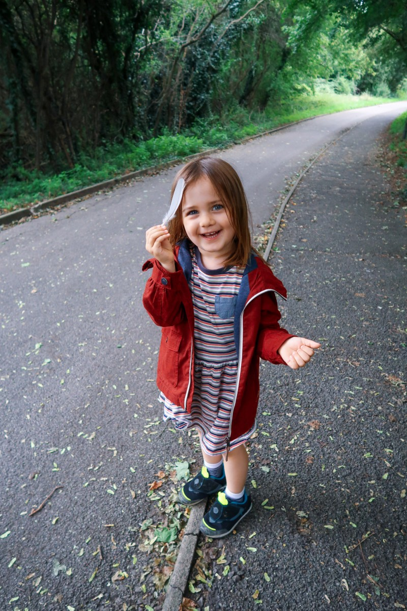 Daisy in a stripy dress, red jacket and black trainers holding a bird feather on a footpath