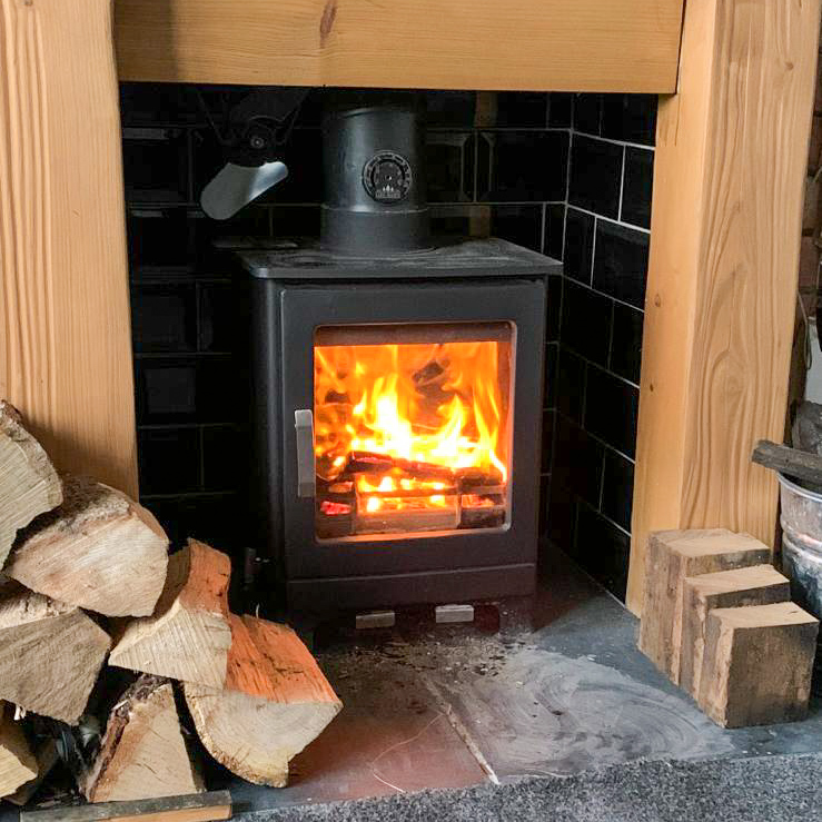 A fireplace with a log burner that is lit and a pile of wood next to it