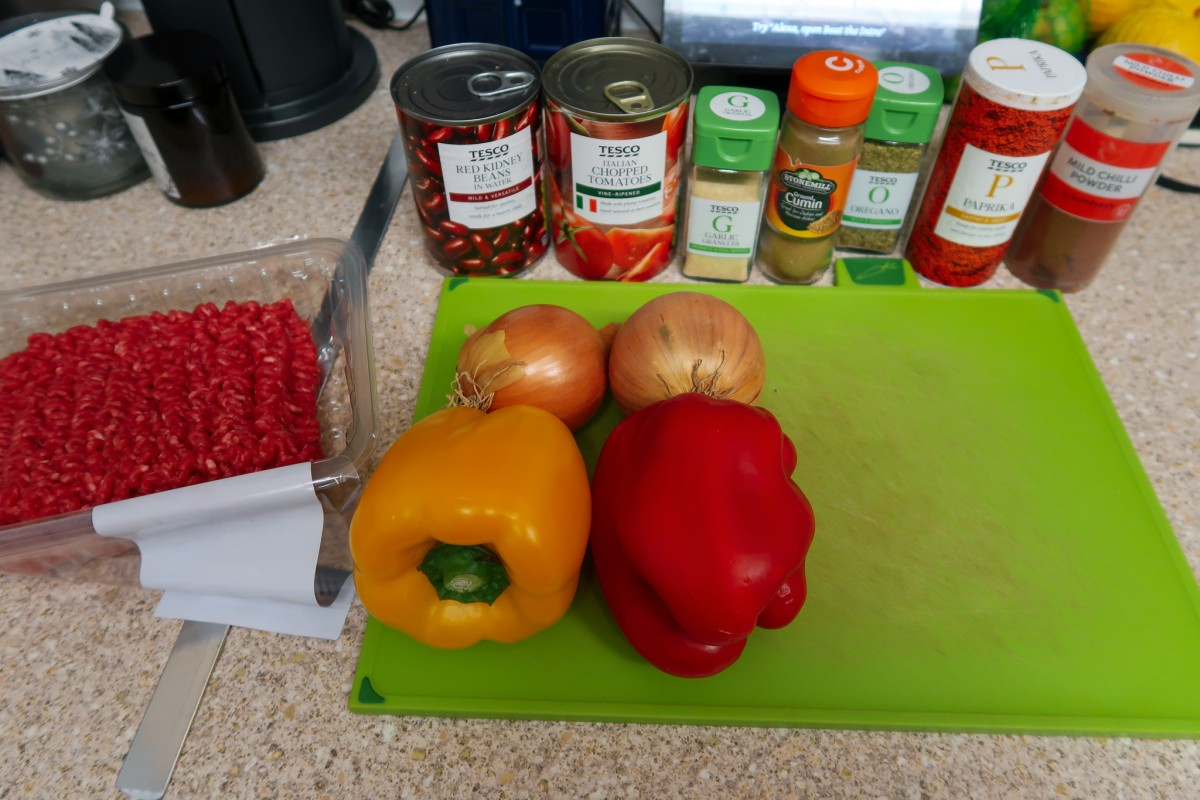 Ingredients for slow cooker beef chilli: beef mince, yellow and red peppers, onions, red kidney beans, chopped tomatoes, garlic granules, ground cumin, oregano, paprika and mild chilli powder alongside a green chopping board