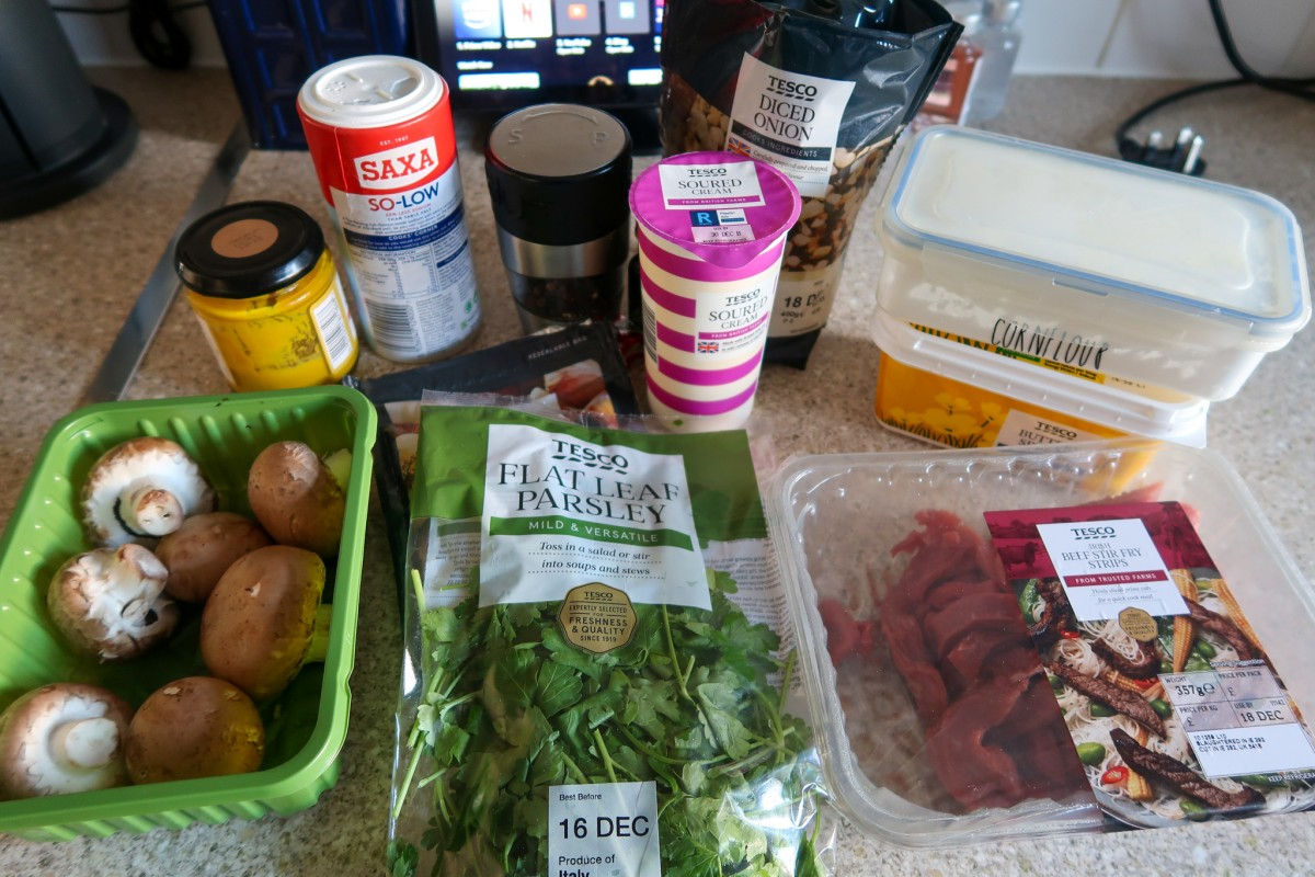 Ingredients for slow cooker beef stroganoff - chestnut mushrooms, mustard, salt, pepper, sour cream, diced onions, cornflour, butter, garlic, parsley and beef stirfry strips