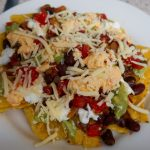 Slow cooker beef chilli with nacho cheese, guacamole, salsa, sour cream and grated cheese