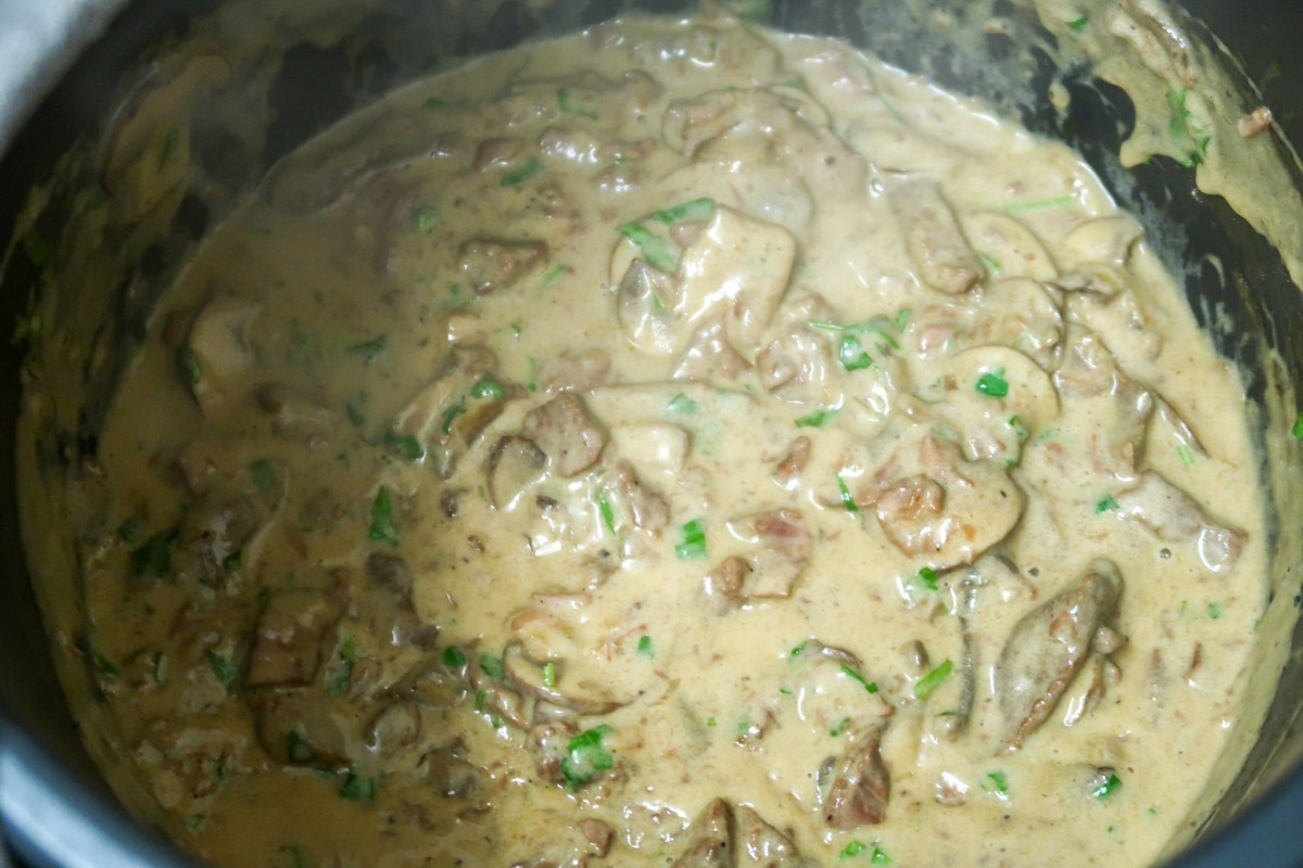 The beef stroganoff base in the slow cooker pot once the sour cream and parsley has been added before the final cooking time