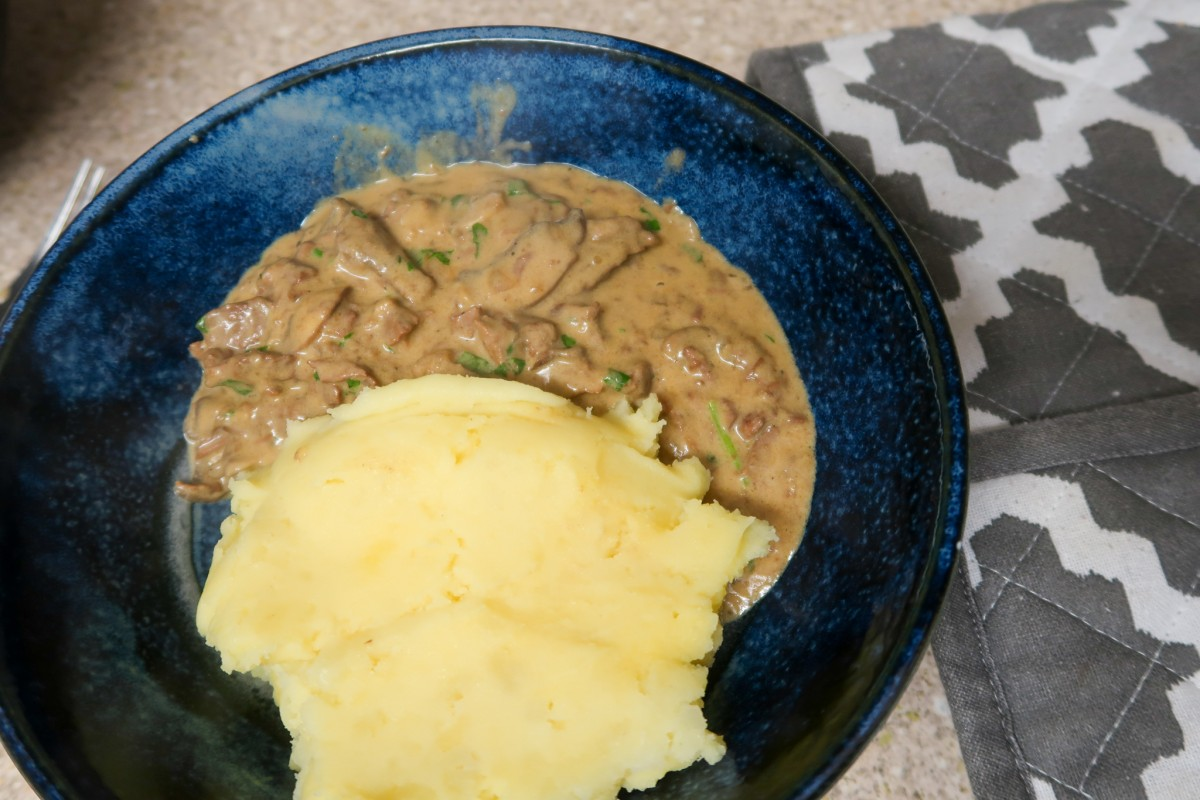 Slow cooker beef stroganoff with mash potato in a blue bowl