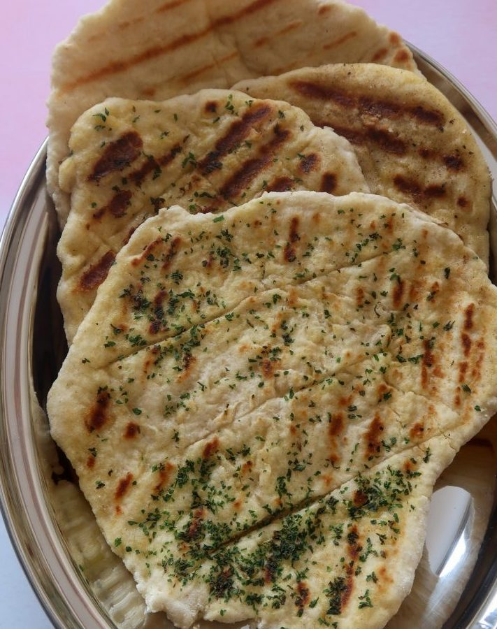 No yeast flatbreads in a silver serving dish - four in total, two with herbs and butter and two plain