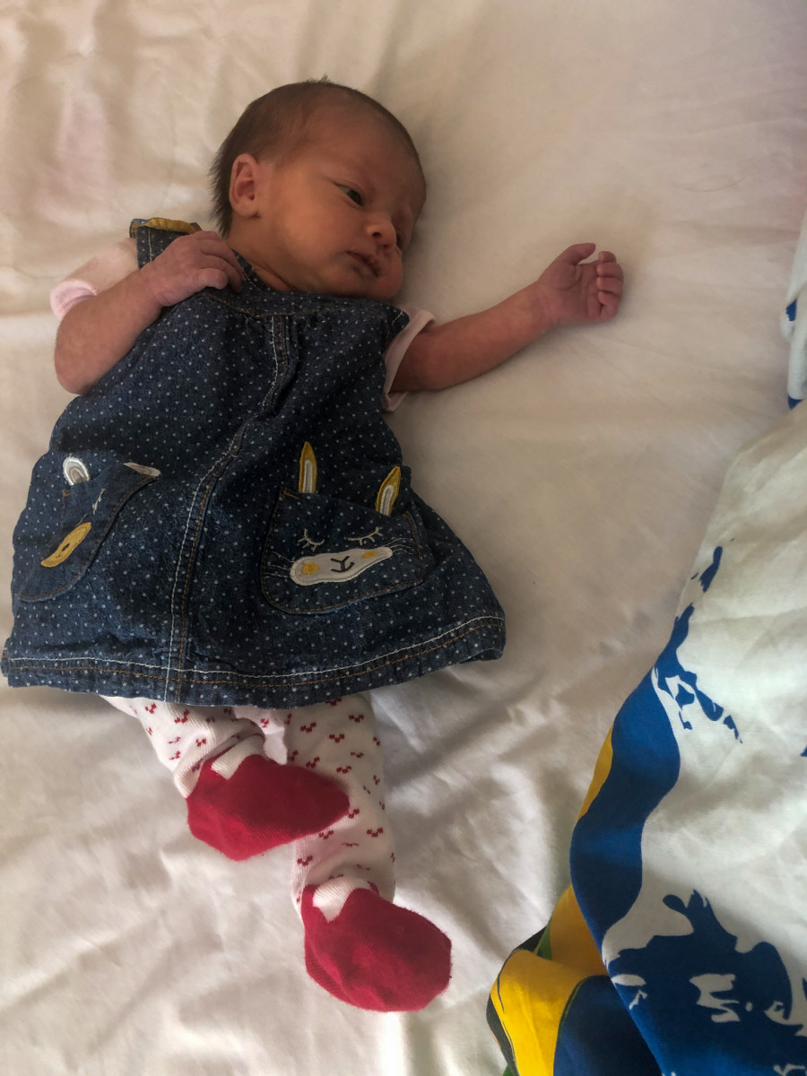 Aurora in her cot wearing blue dungarees and red and pink tights